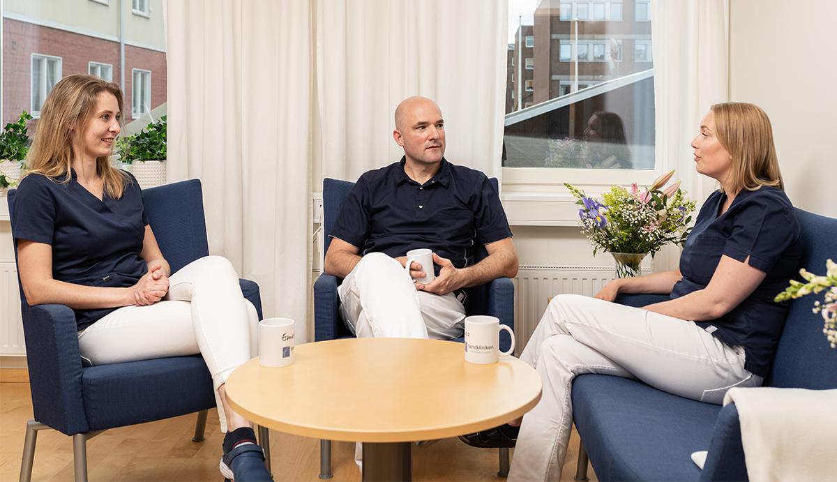 Tre medarbetare dricker kaffe under en konversation i fikarummet